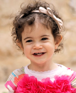 child smiling in a flowered dress